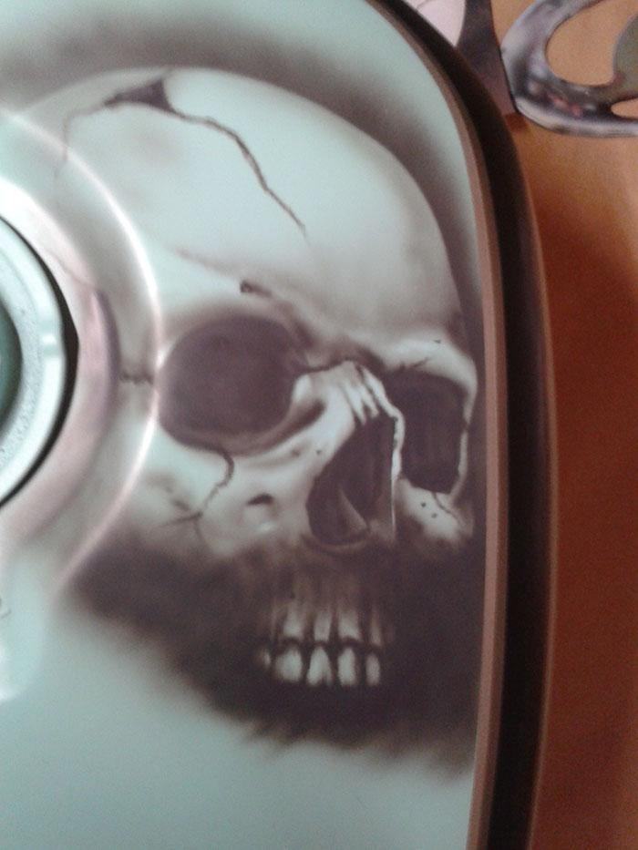 Photo d'un crâne à l'aérographe sur un réservoir de moto